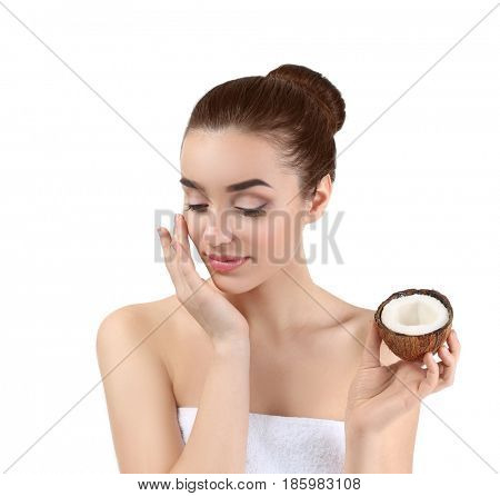 Beautiful young woman applying coconut oil onto skin on white background