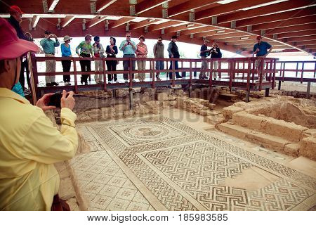 Kourion, Cyprus - March, 2013: Tourists walking and watching ancient floor mosaic. Kourion was an ancient city on the southwestern coast of Cyprus