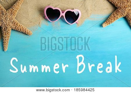 Text SUMMER BREAK, sand and sunglasses on wooden background