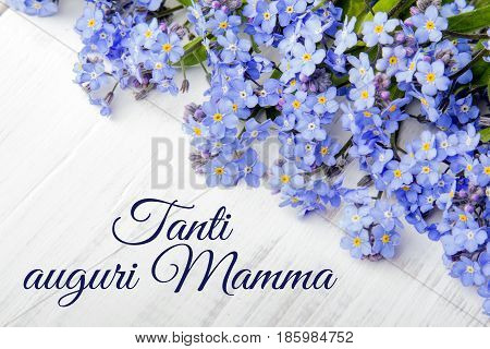 Mother's Day card with Italian words: Happy Mother's Day and blue flowers frame on white wooden background