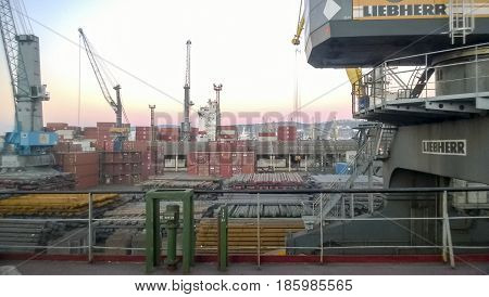 Industrial Landscape Of Developed Seaport Infrastructure. Port Cranes And Vessels, Warehouses And Do