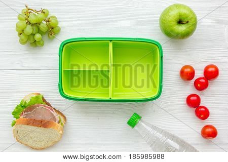 healthy food in lunchbox for dinner at school on white wooden table background top view