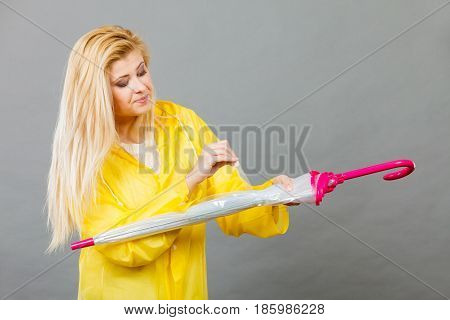 Woman Wearing Raincoat Closing Umbrella