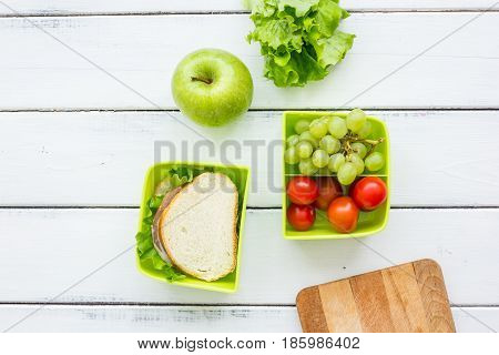 school lunch set with apple and vegetables in lunchbox on white wooden table background top view