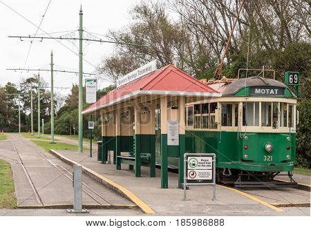 Auckland New Zealand - March 5 2017: Green and yellow antique tramway at its stop on road between Museum of Transport and Aviation Display Hall. Green vegetation Electrical wiring.