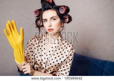 girl in her home clothes dressing gown and runners on her head puts on a yellow glove to clean the house and wash the floor. Concept of hand protection