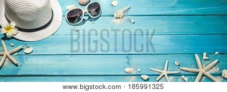 Straw hat, sun glasses and seashells on blue wooden background