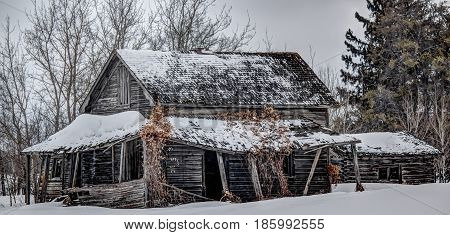 abandoned home  with a sagging porch on a winter day