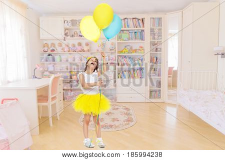 Pretty little blonde girl in a short bright yellow skirt and white blouse.Girl holds in hands balloons , She looks at them from the bottom up.In the children's room.