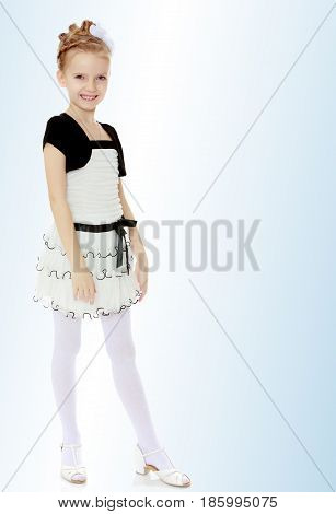 Beautiful little blonde girl dressed in a white short dress with black sleeves and a black belt.The girl is thrusting the leg.On the pale blue background.