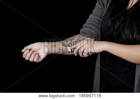 Quito, Ecuador - May 09, 2017: Close up of a woman cutting her arm with a knife, social suicide concept as a sociology metaphor for crowd or herd mentality and group decisions resulting in violence or population death as a network of connected..