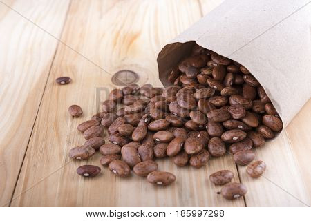 uncooked pinto beans in paper bag and on wooden table