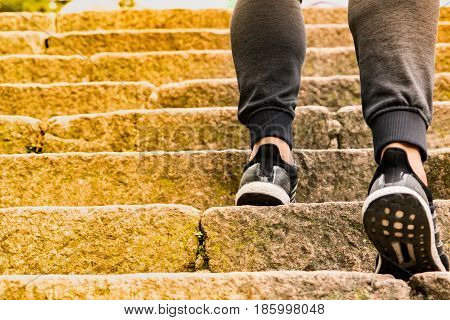 A man climbing the stone steps to success
