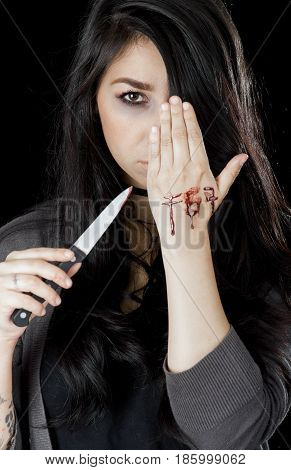 Quito, Ecuador - May 09, 2017: Close up of an anxious teenager in day 1 blue whale challenge writing the word f57 in her hand with a knife and she cover her face with her hair, social suicide concept as a sociology metaphor for crowd or herd mentality and