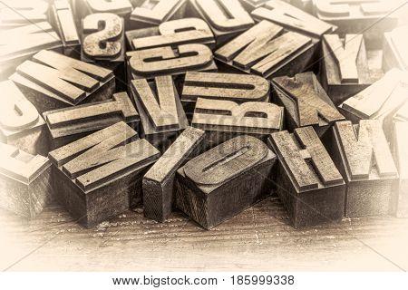 random vintage letterpress printing blocks on a grunge rustic wood, retro opalotype toning