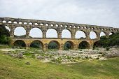 Pont du Gard in Provence France over the Gardon river is an 160 foot high roman aqueduct built to provide water to the city of Nimes from the river Eure near Uzes in the first century A.D. poster