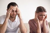 Stressed frustrated couple touching head with eyes closed, feeling strong headache or tired of arguing, exhausted man and woman trying to concentrate, lack of sleep result, hangover effect, bad day poster