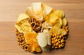 Salty snacks. Pretzels chips crackers. top view poster