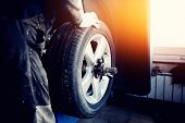 repairman balances the wheel and installs the tubeless tire of the car on the balancer in the workshop. poster