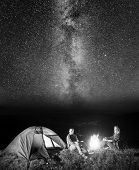 Tourist couple - girl and guy sitting near campfire and glowing tent under incredibly beautiful starry sky at night. Black and white poster