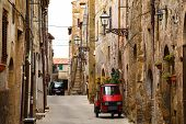 Piaggio Ape standing at the empty street of old italian town poster