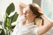 Beautiful woman dreaming with closed eyes in office chair. Businesswoman feels relaxed after busy working day. Female leaning back in chair with hands behind head. Satisfied girl resting at workplace poster