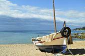 an old fishing boat stranded in the quiet beach Platja de Sa Caleta in Lloret de Mar, in the Costa Brava, Spain poster
