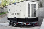 Industrial Diesel Generator. Standby generator. Industrial Diesel Generator for Office Building connected to the Control Panel with Cable Wire. Backup Generator Power. poster