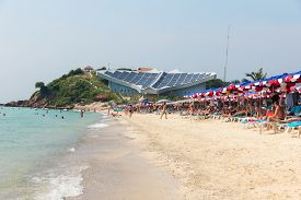 Chonburi, Thailand - November 2, 2012: Samae Beach Famous Beach in Ko Lan near Pattaya City. With Stingray-Shaped Building on Top with Solar Panel and Tourists on the Beach.