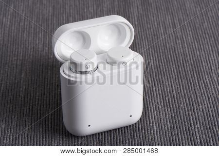 Wireless Cordless Bluetooth Earbuds With Chargeable Case On A Fabric Background