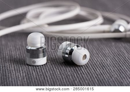 Wireless Cordless Bluetooth Earbuds On A Background Of Cable Earphone