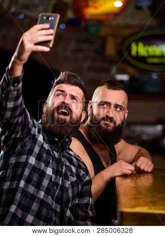 Man Bearded Hipster Hold Smartphone. Taking Selfie Concept. Send Selfie To Friends Social Networks.