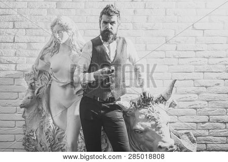 Sculpture, business, architecture. Visitor in gallery, travel. Man critic at historical statue, heritage, property. Bearded man collector drink whiskey at plaster statue. Art exposition, antique. poster