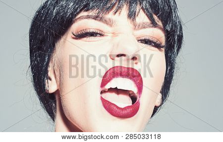 Woman With Attractive Red Lips Shouting. Lady In Black Wig With Make Up On Grey Background. Scandalo