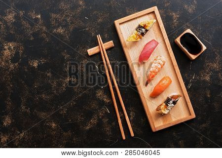 Assorted Sushi Set On A Dark Rustic Background. Japanese Food Sushi On A Wooden Plate, Soy Sauce, Ch