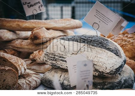 Fresh artisan charcoal bread on sale at a street market, selective focus. poster