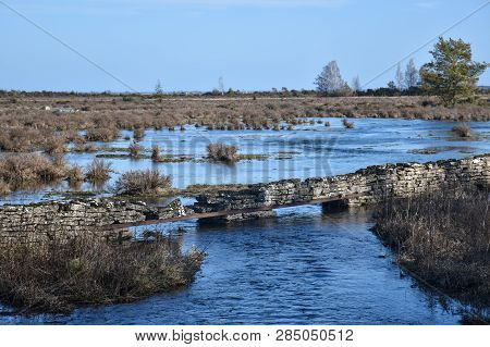 Flooded Great Plain Landscape With Grass Tufts And An Old Stone Wall By Springtime At The Swedish Is