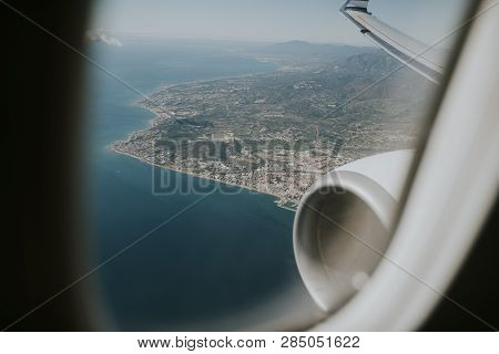 Airplane Engine And Wing, And Costa Del Sol Sea Shore Viewed From A Plane Through The Plane Window,
