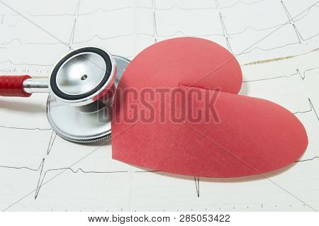 Red Stethoscope And Shape Of Red Paper Heart Lie Side By Side On Lines Of Printed Ecg, Symbolizing H