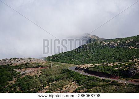 Landscape Of Empty Road In The Mountains Against Dense Clouds. Pico Do Arieiro On Portuguese Island