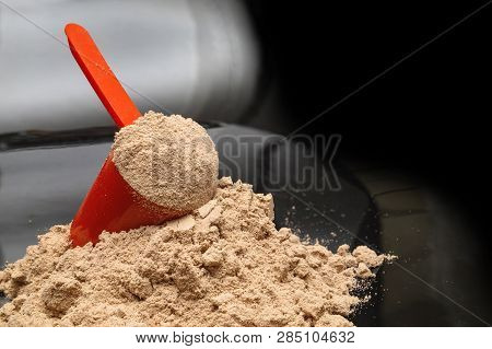 Whey Protein Powder With Red Plastic Scoop On Isolated Black Background.