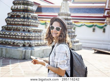 Young Beautiful Happy Smiling European Woman In A Hat And Glasses At A Buddhist Temple In Bangkok Tr