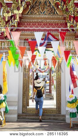 Woman Tourist Traveler In Hat Walks Into A Buddhist Temple In Bangkok, Traveling To Asia