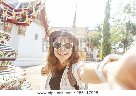 Young Beautiful Happy Smiling European Tourist Woman In A Hat And Glasses At A Buddhist Temple In Ba
