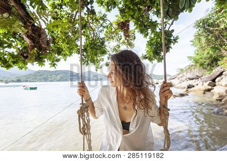 Beautiful Young Woman Traveler Swinging On A Swing On A Tropical Island In The Background Of Amazing