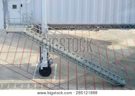Metal Stairway Between Aero Bridge And Ground, Parking At The Designed Position At The Airport