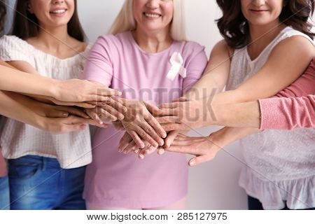 Group Of Women With Silk Ribbons Joining Hands, Closeup. Breast Cancer Awareness Concept