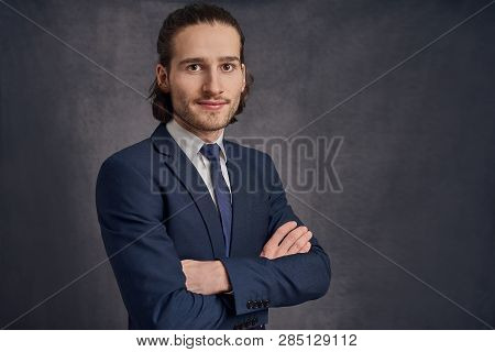 Handsome Young Man With Long Haircut In Business Suit With Blue Necktie, Standing With His Arms Cros