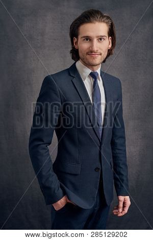 Handsome Young Man With Long Haircut In Business Suit With Blue Necktie, Standing And Looking At The