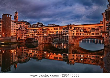 poster of Florence, Tuscany, Italy: view at twilight of the landmark Ponte Vecchio, the famous medieval bridge over the Arno river with old shops of artisan goldsmiths and jewelers